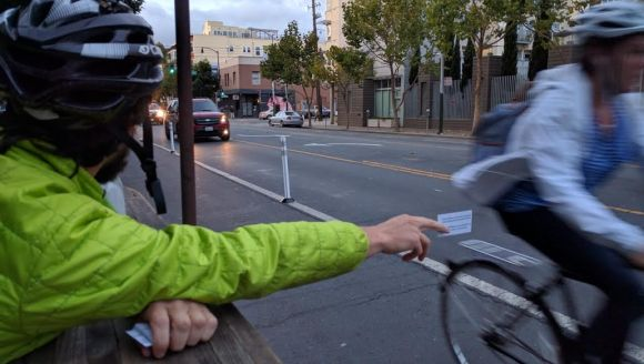 """Cone Guy"" hands out SFMTrA information cards to passing cyclists. Photo: Streetsblog"