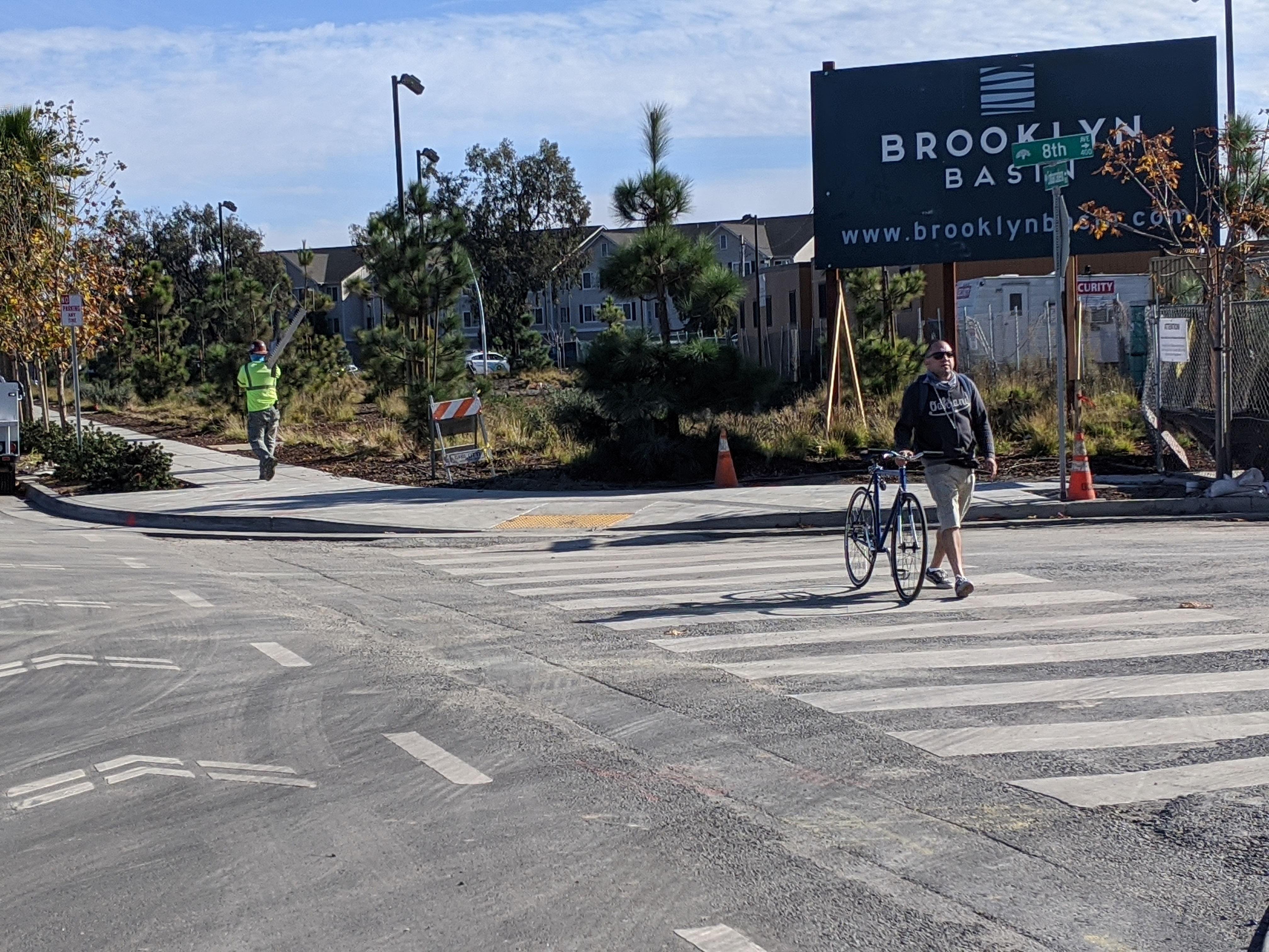 A cyclist, perhaps too intimidated by the heavy traffic and blocked bike lanes, walking his bike outside of Brookyn Basin