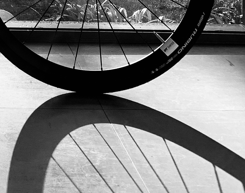 Bicycle wheel against the sun and it's shadow
