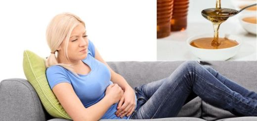 Blond woman feeling stomach pain seated on a gray sofa isolated