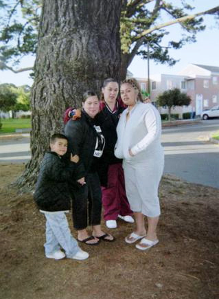 On the first anniversary of the police murder of Asa Sullivan, family and friends gathered for a vigil near the apartment where he his life was stolen. Shown here, from left, are Little Asa, Nicole, Evonne, a close family friend, and T-sha.