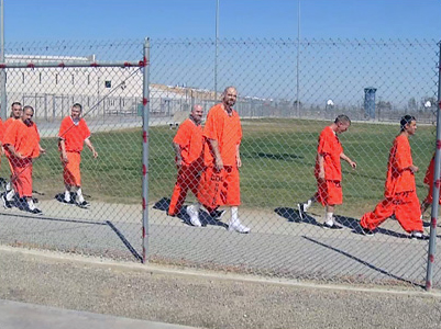 North Kern State Prison prisoners walk along fence line