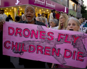 'Drones fly children die' protest march banner Black man