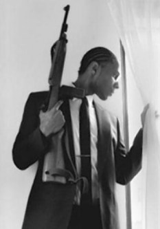 Malcolm Shabazz in replica of Malcolm X at window with rifle, pic posted to Malcolm's Twitter page