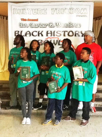 Dr. Carter G. Woodson Black History Bowl middle school div. winners Ile' Omode College Prep, coach Baba Jahi, Yafeu in red