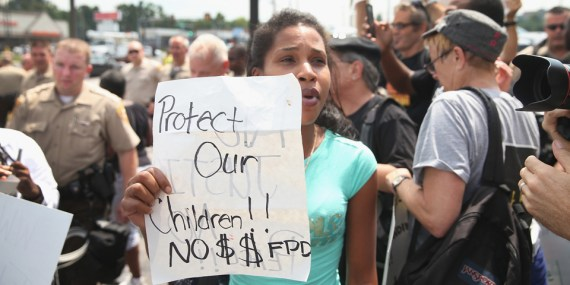 In a chaotic crowd of well-paid media and police, a resident of Ferguson, a suburb where the poverty rate doubled in three years and the unemployment rate rocketed from less 5 percent to over 13 percent in two years, demands that no tax money be spent on the Ferguson Police Department when it murders children instead of protecting them. – Photo: Scott Olson