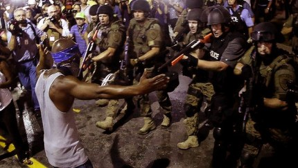 Soldiers and riot cops aim all their fire power at one lone protester in Ferguson. – Photo: AP