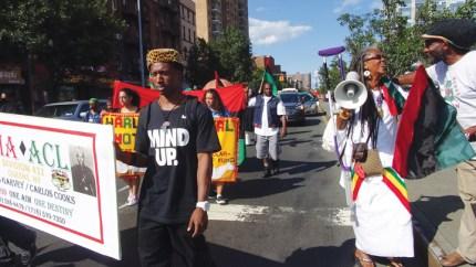 UNIA Centennial celebrants parade down Malcolm X Boulevard in Harlem. – Photo: Wanda Sabir
