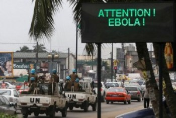 U.N. troops patrolling Abidjan, Ivory Coast, pass a sign warning of Ebola. Africa needs healers, not soldiers.