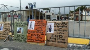 Demonstrators boldly placed signs decrying long-term solitary confinement against the barricades set up to keep the prisoner supporters away from the main gate during the large Occupy San Quentin rally on Feb. 20, 2012. – Photo: Bastique, Flickr