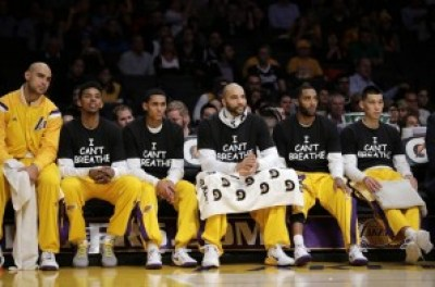 """Lakers, from right, Jeremy Lin, Wayne Ellington, Carlos Boozer, Jordan Clarkson and Nick Young wear """"I can't breathe"""" T-shirts as they sit on the bench during the first half of their Dec. 9 game against the Kings. – Photo: Jae C. Hong, AP"""
