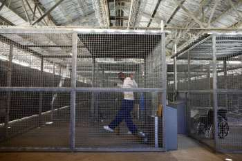 These San Quentin exercise cages are covered with a roof that allows in sunlight only through rust holes and keeps out the prying eyes of visitors. – Photo: Lucy Nicholson, Reuters