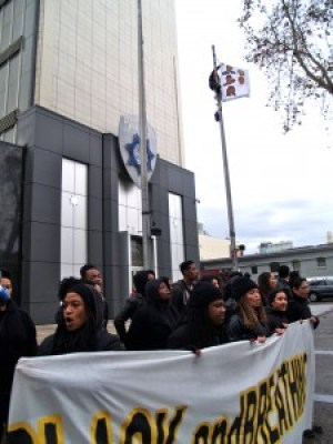 As a contingent of Black protest leaders chanted below, an experienced climber used his gear to carry a banner up the OPD flagpole and unfurl it, revealing pictures of four young men murdered by police. He stayed there for hours, as chained protesters ringed the base of the flagpole. – Photo: BaySolidarity