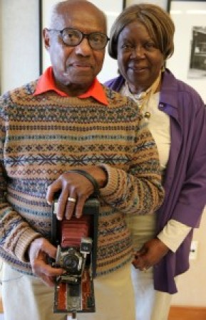 David Johnson, holding his first camera, and his wife and biographer, Jacqueline Annette Sue Johnson, were the stars of the show at the reception for an exhibition of his work at the Harvey Milk Photography Center on Oct. 15, 2014. – Photo: Malaika Kambon