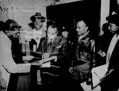 """Edward G. Robinson signs autographs at Leola King's Blue Mirror on Fillmore. Asked why a web search finds almost no photos of Mrs. King or her businesses, Lance Burton says: """"Most of Mrs. King's mementos were destroyed by the Redevelopment Agency, both at her house and at the Bird Cage, where she also had items from the Blue Mirror. They were brutal, as you know, about shutting her down. Then, what they did keep to archive was virtually ransacked at the Redevelopment offices. I spent a month going through boxes at the SFR and found nothing. I have a few pix from the club but terrible quality – water stained, blotched  and low quality."""" This is one of them."""