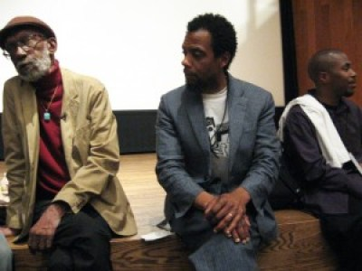 "With the visit of Sam Greenlee, celebrated – and persecuted – for his film, ""The Spook Who Sat by the Door,"" on April 8, 2012, not long before he died, the Oakland International Film Festival made history. Here are Greenlee, David Roach and The People's Minister of Information JR at the Oakland Museum, where the festival was held that year."