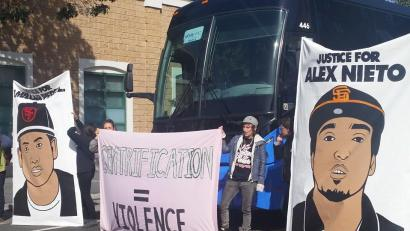 "The dramatic shutdown of the Mission Police Station in San Francisco on March 23 also corralled an eBay shuttle bus, which was then decorated with poster images of SFPD murder victims Amilcar Perez Lopez and Alex Nieto. Erin MC from the Anti-Eviction Mapping Project is holding the ""Gentrification = Violence"" banner. – Photo: PNN"