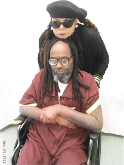 This picture, taken April 9 in the prison visiting room, shows Mumia to be very weak and very thin. Since then, he has been moved from the infirmary back to his cell and has quickly deteriorated further. No longer allowed a wheelchair, he can barely walk in baby steps, yet must go the equivalent distance of three blocks to reach the infirmary and two blocks to meals.