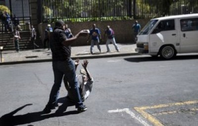 A taxi driver throws rocks at a man on the ground in the April 15 conflict in Johannesburg. – Photo: Marco Longari