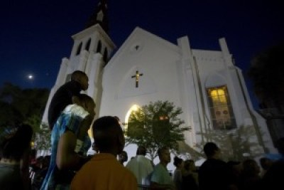 Outside Mother Emanuel on June 20, church folks sing and pray for the nine souls assassinated June 17, including their pastor, Rev. and state Sen. Clementa Pinckney. – Photo: Carlo Allegri, Reuters