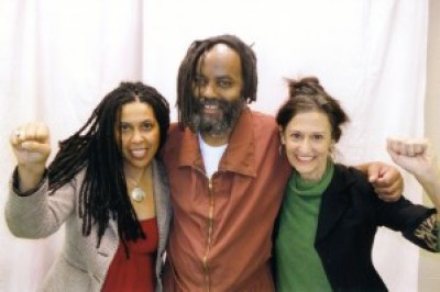 See how Mumia's appearance has changed – deteriorated – in the three years since he was released from death row. Here, Johanna Fernandez and her friend, attorney Heidi Boghosian, visit Mumia on Feb. 7, 2012, shortly after his release.