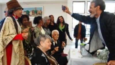"Michael's brother, Ted Lange, star of the long-running TV series ""Love Boat,"" takes a picture at the festive repast. – Photo: Wanda Sabir"