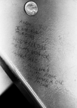 """This is the entire message that Aaron scratched on the underside of a bench as he was being tortured: """"Aaron – I lie about murders. Police threaten me with violence, slapped and suffocated (illegible) plastic. No lawyer or (illegible). No phone."""""""