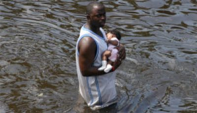 A man carries a baby after the Superdome was evacuated following Hurricane Katrina in New Orleans. – Photo: U.S. Navy
