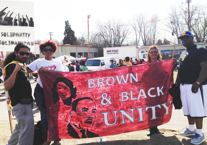 Manuel La Fontaine, left, holds the banner that All of Us or None carried 2,400 miles to join the Selma March 50th anniversary in March 2015. Beside him is Flora Johnson of Huntsville, Ala., and, at the far right, Askari Amin of All of Us or None.