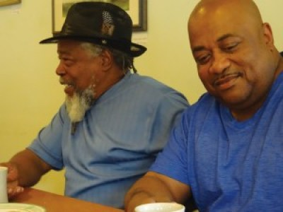 Malik Rahim and Michael Mable, Albert Woodfox's brother, at a coffee shop across from the courthouse waiting for the hearing on Albert July 6. – Photo: Wanda Sabir