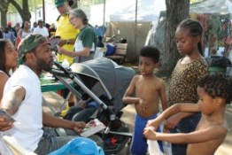 Sulay, the son of political prisoner Abdul Majid, was giving a political education class to Xion and her brothers at the political prisoner booth at the International African Arts Festival in Brooklyn on July 4. – Photo: JR Valrey, Block Report
