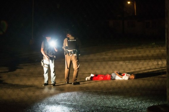 """Tyrone Harris Jr., 18, who his father says was """"very close"""" to Michael Brown, lies critically wounded by cops on the ground one year to the day after Brown's death, Aug. 9, 2015. The photo is eerily similar to that of Michael Brown as he lay dead on the ground for four and a half hours after being shot eight times by cop Darren Wilson."""