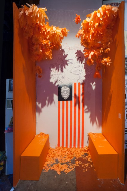 """""""Sandra Bland"""" in orange reflects the orange jumpsuit she wore in her last photo, dignifying that humiliating symbol, reminding the viewer she was a person, not a criminal. – Photo: J. Astra Brinkmann"""