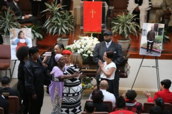 Gwendolyn Woods, center, the mother of Mario Woods, gets a hug at the Cornerstone Missionary Baptist Church during the funeral for her son Thursday, December 17, 2015. Woods was shot and killed by police directly across the street from the church earlier this month. (Mike Koozmin/S.F. Examiner)