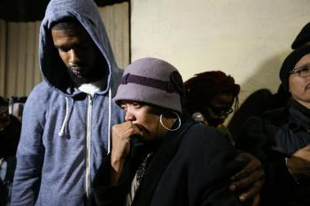 At the vigil where Mario Woods had been executed by SFPD the day before, Mario's cousin Jeff Steward comforts Mario's mother, Gwendolyn Woods, as hundreds gather 'round to support them. – Photo: Poor News Network
