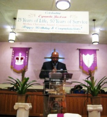 Bishop Ernest Jackson, Espanola's pastor at Grace Tabernacle Community Church, preaches beneath a banner wishing her a happy 75th birthday, on Feb. 9, 2008. – Photo: Francisco Da Costa