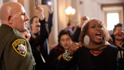 Sala-Haquekyah Chandler leads a chant picked up by protesters scattered all around the rotunda, drowning out the inaugural ceremony and perplexing the army of sheriff's deputies. – Photo: Noé Serfaty