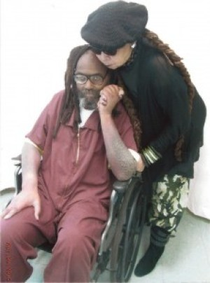 "Mumia's wife, Wadiya Jamal, hugs him during a visit on April 9, 2015. This photo shows the terrible, ""elephant-skin"" rash on his arms."