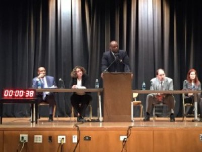 """Troy Williams speaks as the other members of the Department of Justice """"listening session"""" panel sit on the stage of the Thurgood Marshall High School auditorium on Feb. 24. – Photo: Hoodline"""