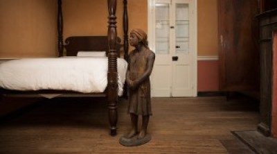 A terra-cotta statue of an enslaved child stands inside the main house at the Whitney Plantation in Wallace, Louisiana. – Photo: © Edmund Fountain, Reuters