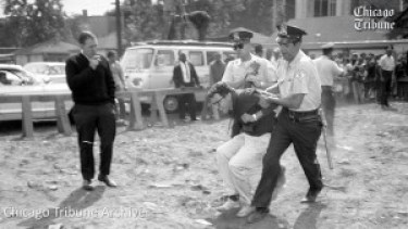 "In August 1963, when Bernie Sanders, then 21, was active with CORE in Chicago, he was arrested after lying down in front of bulldozers at a protest against a Black neighborhood school proposed to have no building, only portables, located between a railroad track and an alley. Of the 159 arrested, he was one of only four found guilty – of resisting arrest – and fined $25. The decision to build the ""school"" was rescinded the day of the March on Washington, Aug. 28, 1963. – Photo: Chicago Tribune"