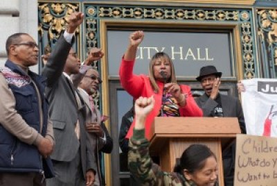 """Fists rise as Justice 4 Mario Woods Co-Chair Phelicia Jones shouts: """"All power to the people! Shame on San Francisco! Shame on the San Francisco Police Department! We are gathered here to bring unity, to fight as one, Black and Brown together, fighting for justice. … We are here to tell the powers that be in San Francisco, you will not get away with murder. … If we can't beat you in court, we'll beat you with our voting ballots!"""" Archbishop Franzo King (right) stands behind her, cheering her on. – Photo: Pax Ahimsa Gethen"""