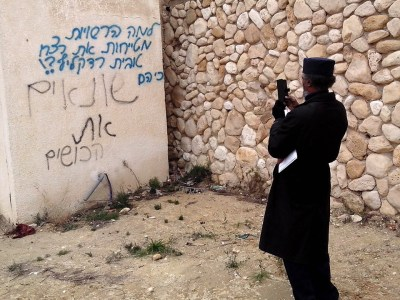 "African Hebrew Israelite spokesperson Immanuel Ben-Yehuda takes a photo of neighborhood graffiti. The top blue section of the graffiti, which was recently added to the wall, reads: ""Why are the authorities covering up the murder of Toveet Radcliffe? Because they…."" The bottom black section of the graffiti, which was sprayed on the wall many years before, reads, ""… hate the n*****s."" – Photo: David Sheen"