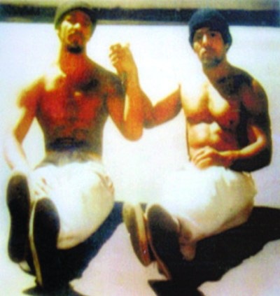 "Two legends of the California Prison Movement, Khatari Gaulden and Hugo ""Yogi"" Pinell, sit in the sunshine in the San Quentin yard in 1976. – Photo courtesy Kiilu Nyasha"
