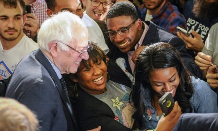 """Bernie is surrounded by supporters at Morehouse College earlier this year. Young Black voters are flocking to him, and older Blacks are recognizing that he is """"unbought and unbossed"""" in the tradition of Shirley Chisholm. – Photo: John Amis, EPA"""