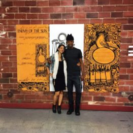 """Martha Alhassen, journalist and PhD candidate at USC, and Greg Thomas, curator and Tufts University professor, embrace after the roundtable discussion in front of """"Sun"""" artwork. – Photo: Omar Ali"""