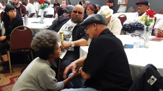 Elilta and David Johnson of the San Quentin 6 share a few words at the memorial for Yogi, as Shabaka Ji Jaga looks on. – Photo: JR Valrey, Block Report