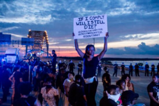 On July 10, 2016, the Sunday after the murders of Alton Sterling and Philando Castile and the cops in Dallas, as protests engulfed the nation, in Memphis, Chanel Trice holds a sign while standing on the cement median between the eastbound and westbound lanes of the Interstate 40 bridge over the Mississippi River. Black Lives Matter supporters brought traffic to a standstill on both sides of the bridge by about 7 p.m. as the estimated crowd on the bridge swelled to more than 1,000. – Photo: Brad Vest, Memphis Commercial Appeal