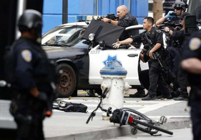 One cop throws a flash bang grenade at a shirtless man lying spread eagle on the sidewalk in downtown San Francisco, at Market and Jones, on June 6, 2016, as other police block off surrounding streets during a four-hour standoff. SFPD was praised for its restraint. – Photo: Connor Radnovich, SF Chronicle