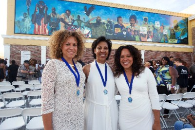 """OneUnited Bank President and COO Teri Williams, center, beams proudly at the unveiling of the mural on the OneUnited Bank in Liberty City, Miami, on July 11, 2015. """"Our hope as an institution is to spark a creative, artistic renaissance here in Liberty City,"""" she says."""